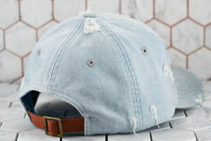 The back view of the 6 panel ripped denim blue baseball cap by Dear Martian, which shows the light brown leather adjustable strap.