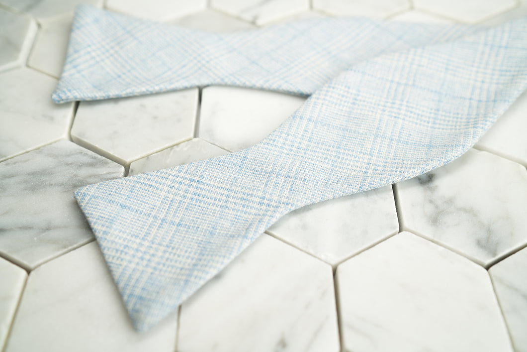 An image of Dear Martian's Tiffany blue glen plaid bow tie untied, lying against a hex tiled background.