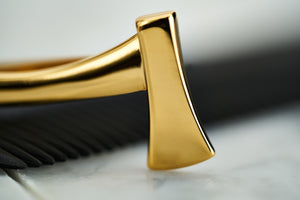 An up close image of the gold Dear Martian ax tie bar accessory for men.