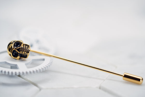 A side view image of the gold plated Vie skull tie clip made by Dear Martian, Brooklyn is laying against a white background.