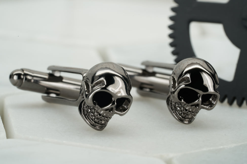 A photo of a pair of Dear Martian gunmetal skull cufflinks.  These  men's cufflinks feature enameled black eyes.