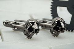 A product image of a pair of vie gunmetal skull cufflinks.