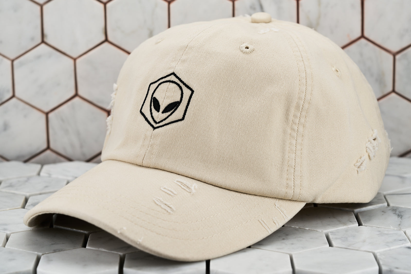 The front view of the ripped up stone khaki martian cap, which features a black embroidered hexagon encompassing an alien.