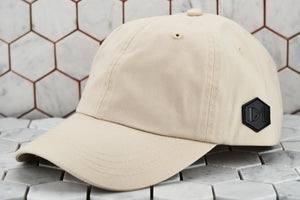 A front image of the stone khaki cotton twill hat by Dear Martian Brooklyn, which portrays the hexagonal leather DM patch logo.