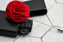 A side image of the salsa red floral lapel pin laying across a black vintage zippo lighter.