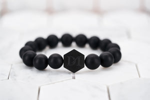 A product image of the men's matte black bead bracelet by Dear Martian with a signature matte black hexagon logo bead.