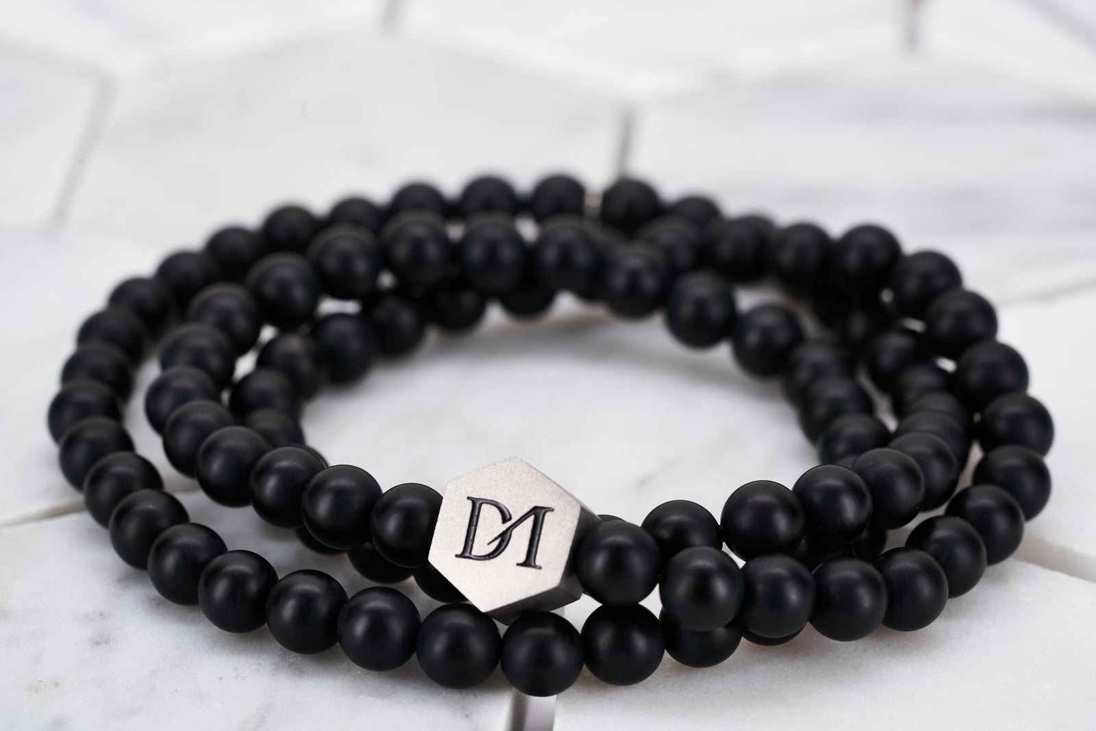 An image of a wrap bracelet made by Dear Martian Brooklyn constructed with matte black obsidian stones that can wrap around the wrist multiple times.