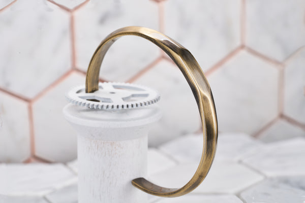 A product image of the Duality vintage brass cuff bracelet by Dear Martian Brooklyn. The image portrays the front hexagon bezel and round cuff.