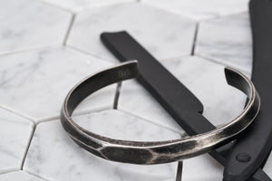 A product image of the Duality antique steel bangle bracelet sitting on top of a matte black painted straight edge razor.