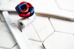 A handmade satin flower lapel pin with red and navy colors constructed by Dear Martian.