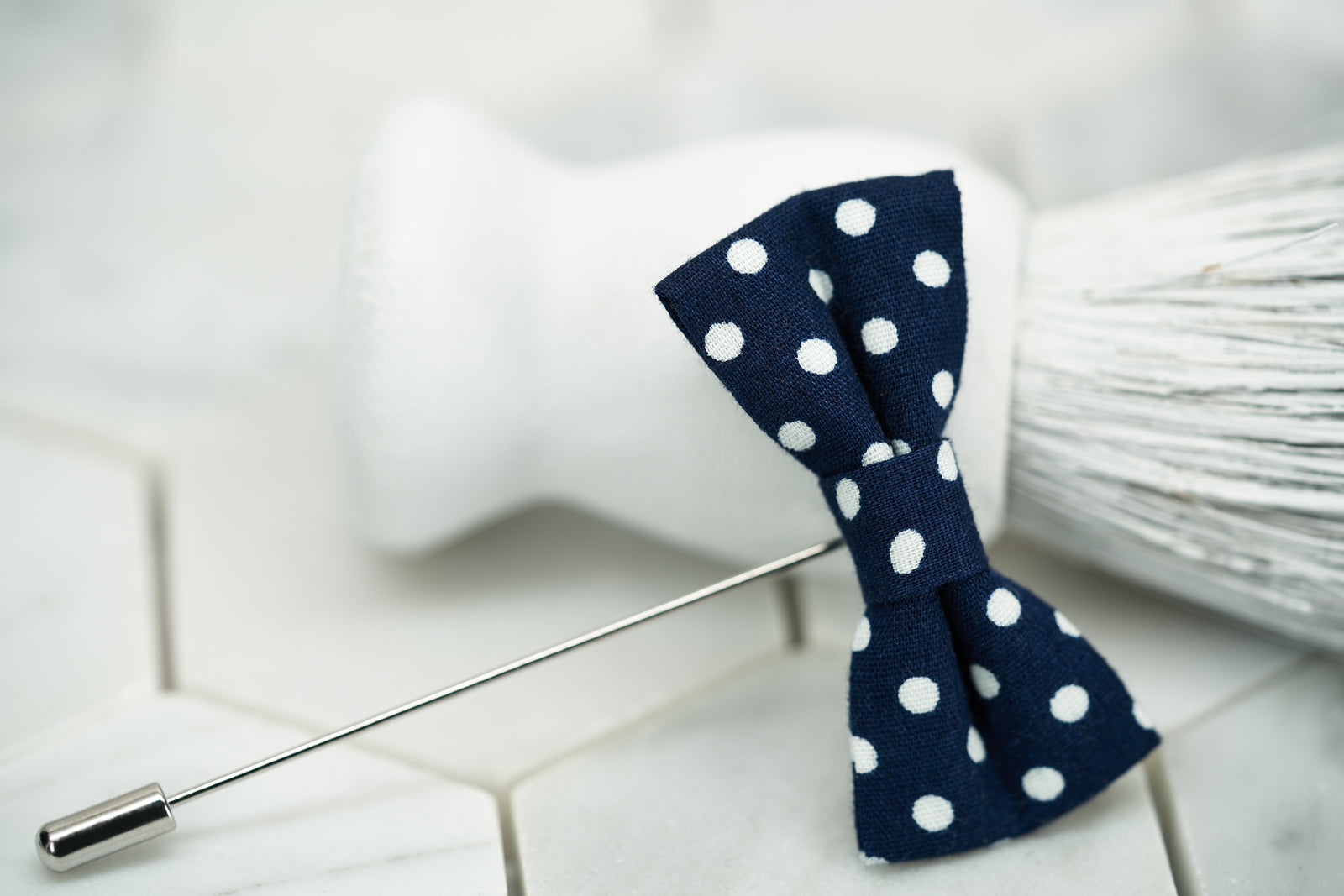 A product image of the navy and blue polka dot lapel pin for men by Dear Martian.