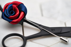 A side view image of the navy red twist flower lapel pin for him.