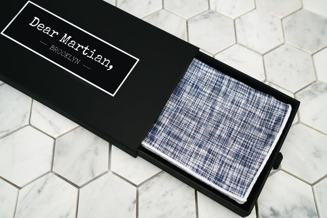 A product image of the Pratt navy pocketsquare inside a matte black pull out gift box, that shows the Dear Martian, Brooklyn logo.
