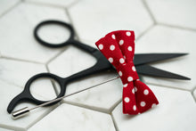 A photo of the Dear Martian white and red polka dot mini bow tie lapel boutonniere.