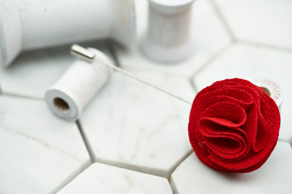 An image of the groomsmen vivid red flower lapel pin handmade by Dear Martian.