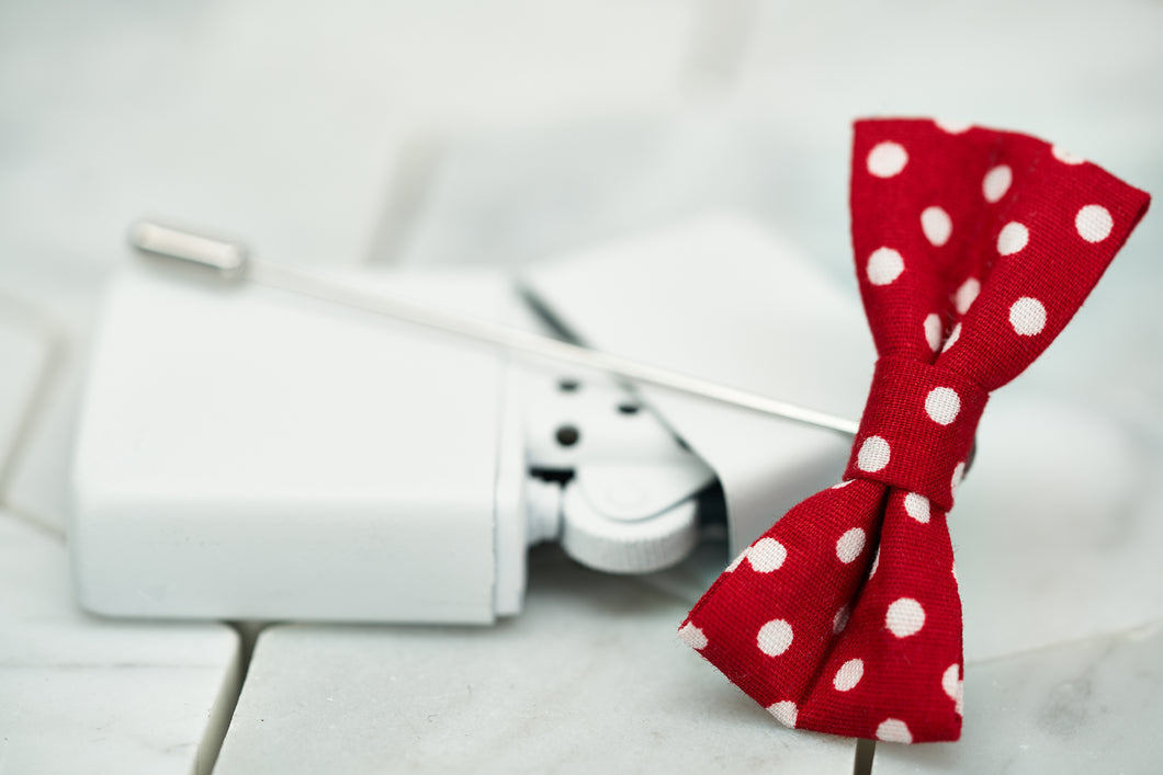 An image of a red polka dotted bow tie lapel pin; sitting on top of a vintage white lighter.