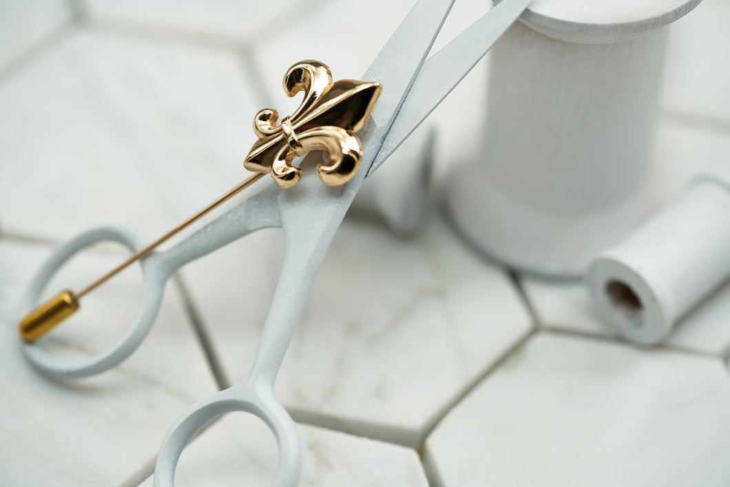 A product image of the gold fleur de lis lapel pin by Dear Martian Brooklyn, which lays upon wooden spools.