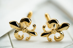 A front image of vintage gold tone brass fleur de lis cufflinks made by Dear Martian, Brooklyn.