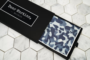 An image of the blue camouflage patterned pocket square inside our Dear Martian, Brooklyn black pull out style box.