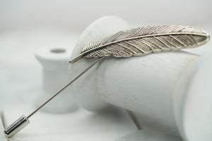 An image of the Dear Martian, Veder; vintage steel feather lapel pin laying against a wooden spool.