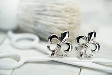 An image of a set of silver cufflinks, which feature a fleur de lis design created by Dear Martian, Brooklyn.