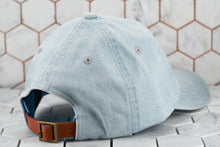 The back view of the Dear Martian solid denim blue dad hat , which shows of the brass buckle adjustable strap closure.