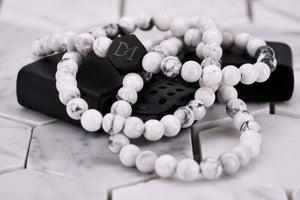 An image of the Dear Martian, BKLYN white howlite wrap bracelet , which features a matte black hexagon logo bead.