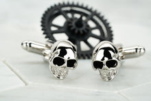 A pair of steel skull cufflinks with enamel eyes made by Dear Martian, Brooklyn. These cufflinks sit against a white hexagonal background.