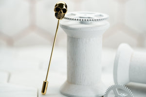 An image of a gold skull suit jacket pin named the Vie by Dear Martian.