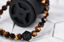 A detailed image of the energy bracelet strung with tigers eye stones.
