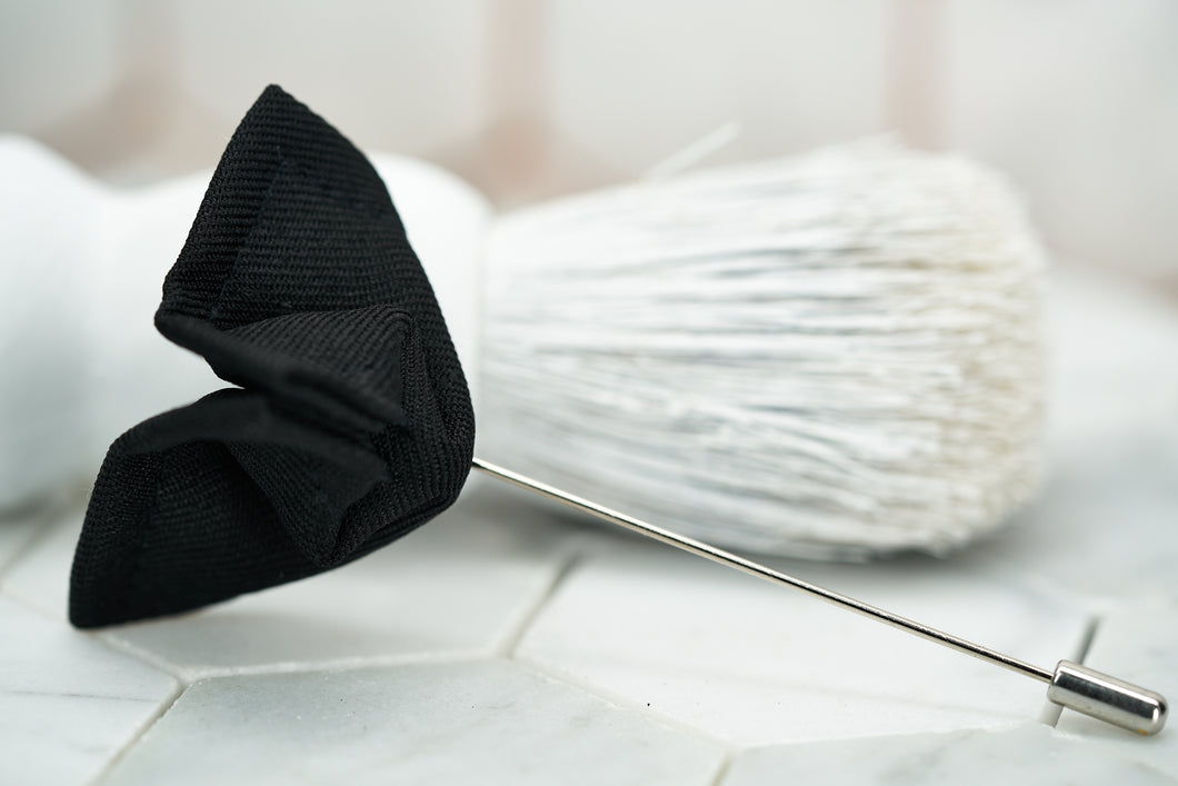 An image of a black butterfly boutonniere pin against a vintage white beard brush by Dear Martian.