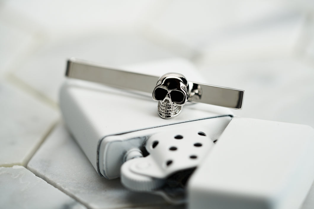 An image of a stainless steel men's skull tie clip handmade from Dear Martian. The tie bar is sitting a top a white spray painted vintage zippo lighter.