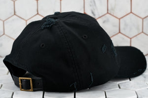 The back view of the distressed raw black dad hat by Dear Martian, Brooklyn; which depicts the leather strap.