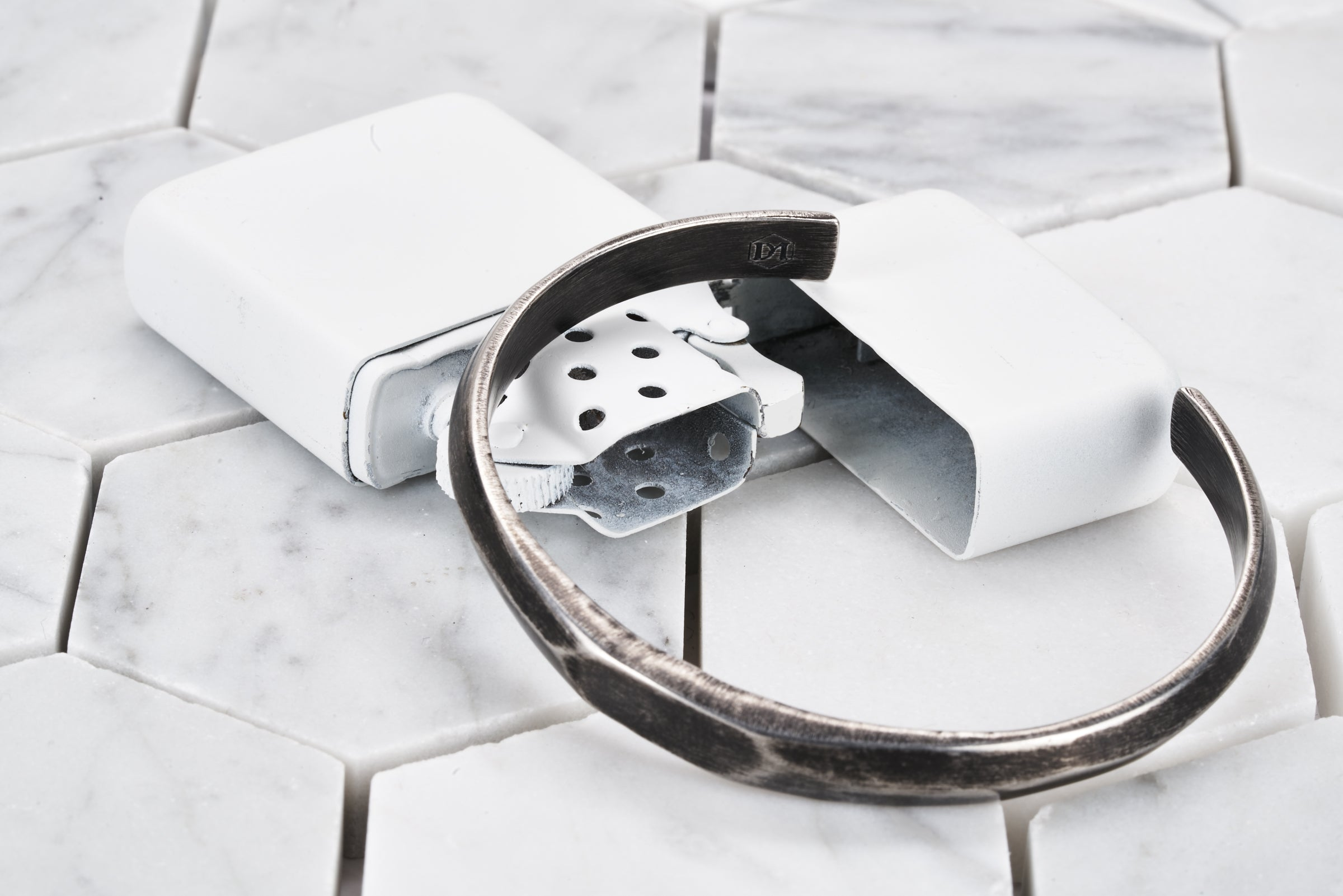 An image of the Duality antique steel cuff bracelet sitting on top of a white zippo lighter. The front of the bracelet shows a wide hexagon front bezel.