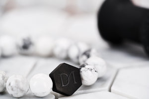A close up image of the Dear Martian signature DM hexagon black logo bead. The bead is strung with chakra white howlite stone beads.