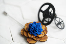 An image of a floral wooden lapel pin with a felt wool blue center by Dear Martian, Brooklyn.