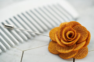 A side view image of the yellow knit summer flower lapel pin.