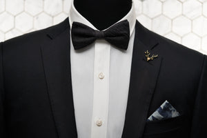 An image of a mannequin dressed dapper in our Strauss Raw bow tie paired with; a gold stag lapel pin, and camo blue denim pocket square.