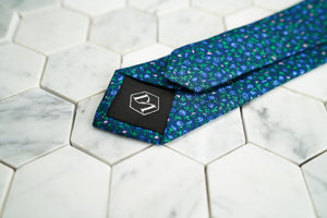 The back of the Dear Martian, Ditsy skinny floral purple tie, featuring a hexagon DM stitched logo.