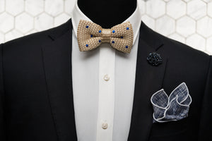 A mannequin is shown wearing a black suit wit our kahki & blue dotted silk knitted bow tie, navy patterned bow tie and matching navy floral lapel pin.