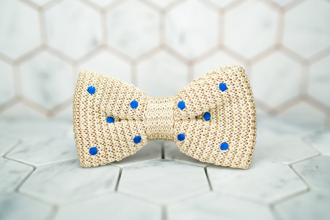 An image of the front of the creme colored, Dear Martian bow tie featuring blue polka dots.