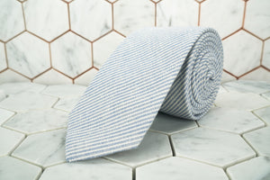A DM exclusive pencil striped linen neck tie; featuring thin grey and white stripes.