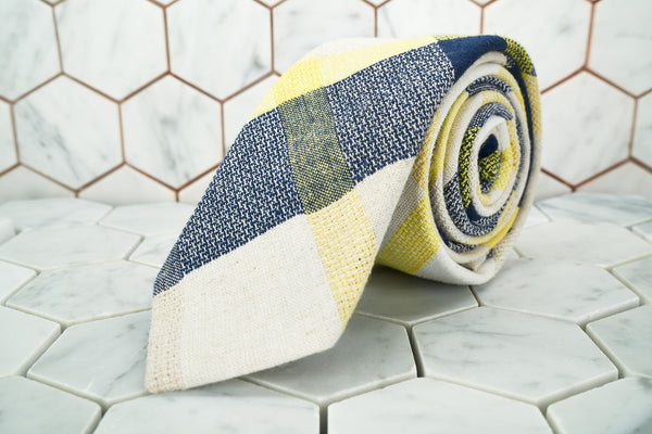 A handmade patterned necktie made by Dear Martian,  Brooklyn is rolled up.