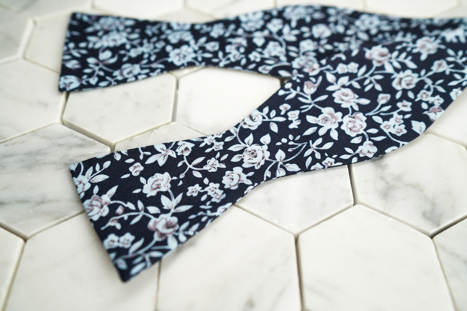 An image of the Dear Martian exclusive Liberty navy floral patterned bow tie; shown across a hexagon background.
