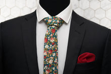 The green floral slim tie from Dear Martian, is paired with a red silk knit pocket square; and displayed on a suited mannequin.