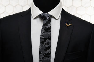 An image of the Dear Martian storm grey tie is shown on a mannequin dressed in a black suit with our antique gold stag lapel pin.