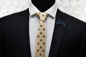 The Dear Martian ivory necktie with embroidered anchors is shown on a mannequin with a suit. The suit features a mini bow polka dot lapel pin.