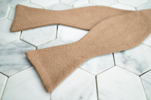 An image of a crepe-linen latte bow tie lying flat and untied against a white hexagonal background.