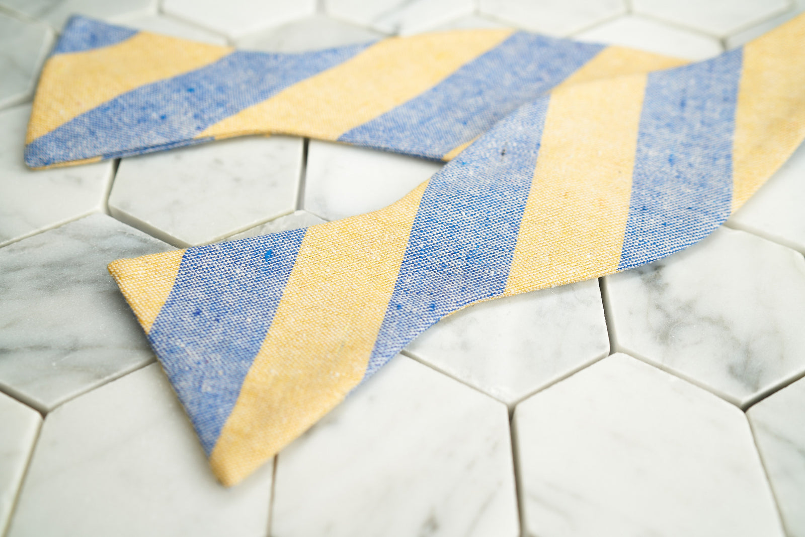An image of the Dear Martian yellow and blue striped linen bow tie; lying flat and untied.