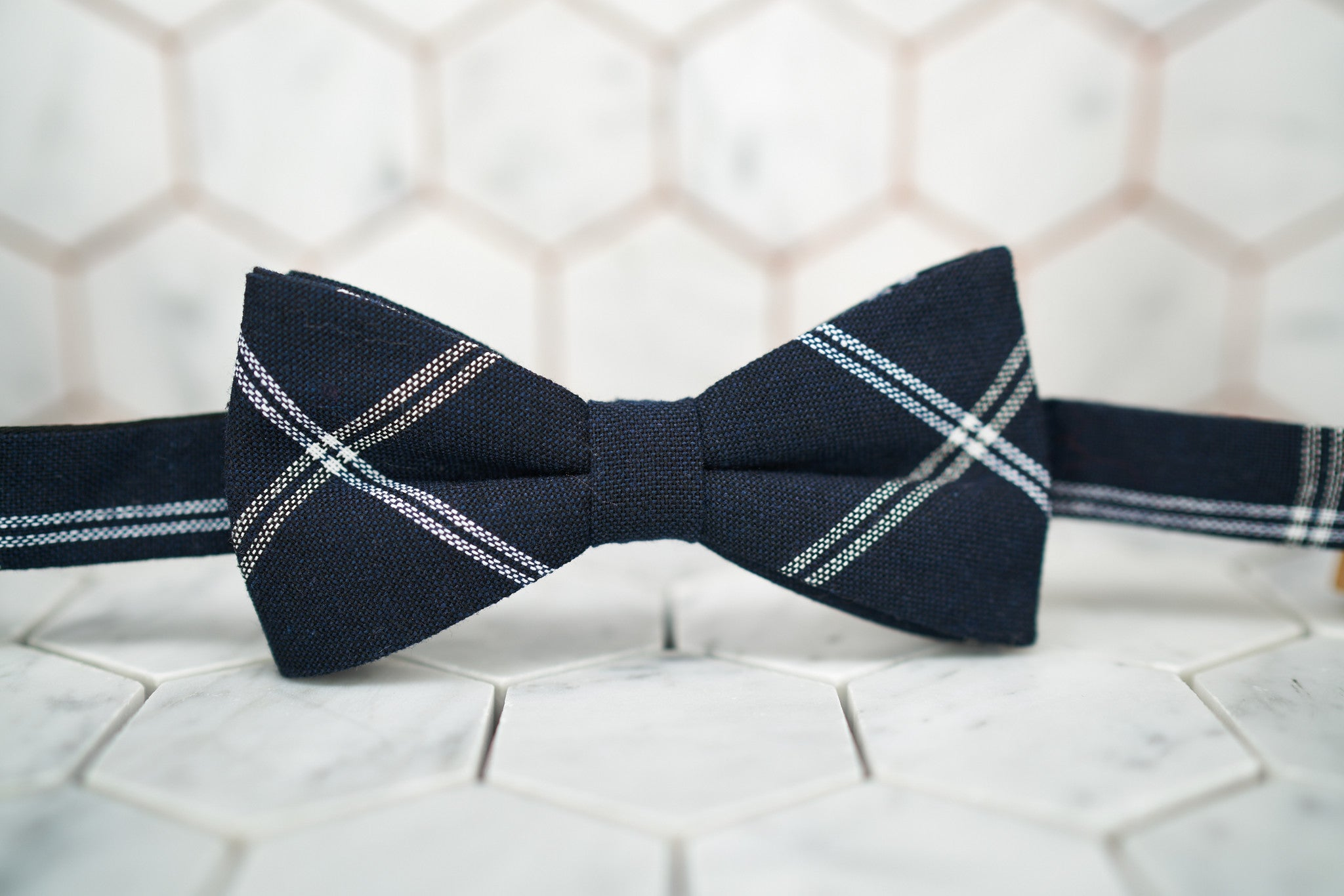 A front image of a minimalist navy bow tie featuring white stripes and a navy background.